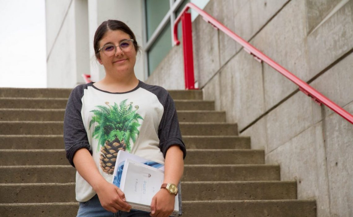Soraya-Bellou-On-campus-stairs-with-books-medium-1024x683